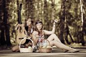 Hippie girls with guitar relaxing outdoor