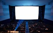 stock photo of cinema auditorium  - Cinema auditorium with people in chairs watching movie. Light of projector. High angle. Frontal view. Ready for adding your own picture.