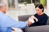 understanding therapist handing tissue to an upset middle aged patient