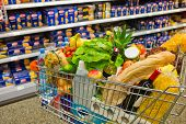 stock photo of local shop  - a shopping cart is a transition between the shelves of a supermarket - JPG
