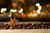 Coffee and Star Anise on sackcloth background with night lights