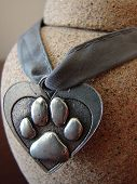 stock photo of bereavement  - a small urn containing a pets ashes with a paw print heart around it - JPG