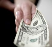 stock photo of bartering  - hand offering payment of ten us dollars cash - JPG