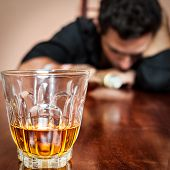 stock photo of alcohol abuse  - Portrait of a drunk  man addicted to alcohol sleeping with his head on the table   - JPG