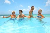 stock photo of infinity pool  - Family of four bathing in swimming pool - JPG