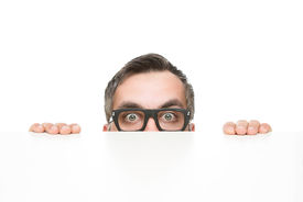 pic of nerds  - Funny nerd peeking from behind the desk isolated on white background with copy space - JPG