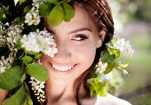 image of apple blossom  - beautiful brunette woman in the park standing near the apple tree on a warm summer day - JPG