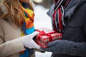 foto of congrats  - Image of gloved hand of guy giving his girlfriend Christmas present - JPG