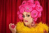 stock photo of drag-queen  - Conceited drag queen with foam pink flower wig - JPG