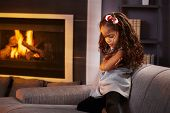image of sulky  - Sulky little afro girl in living room by fireplace - JPG