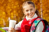 pic of 11 year old  - Close portrait of happy blond 11 years old girl with amazing smile drinking coffee sitting on the bench in the autumn park on sunny day - JPG