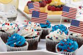image of chocolate muffin  - Chocolate muffins with white and blue icing on 4th of July in patriotic theme - JPG
