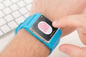 image of fingerprint  - Man is scanning fingerprint for mobile security with blue smart watch - JPG