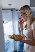 stock photo of lame  - Young Woman Eating Cookies From Refrigerator At Night - JPG