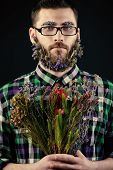 stock photo of greenpeace  - Handsome young man in spectacles and a beard of flowers - JPG