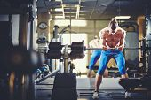 foto of topless  - Portrait of sporty topless man lifting weight in gym - JPG