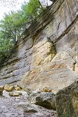 pic of illinois  - large sandstone cliffs with rocks that have fallen in the past turning into powder on the ground St Louis State Park Illinois - JPG