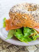 stock photo of bagel  - Fresh Salmon Bagel with fresh cheese and fresh lettuce on table - JPG