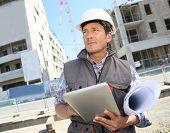 stock photo of entrepreneur  - Entrepreneur on building site using tablet - JPG