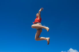 pic of parkour  - Teen girl jumping parkour style off of a concrete wall onto the beach - JPG
