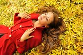 image of coat  - Attractive young woman in red coat lying in autumn leaves - JPG