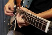 picture of fret  - close up shot of a man with his fingers on the frets of a guitar playing - JPG