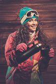 picture of thermos  - Happy woman in ski wear with thermos against wooden wall - JPG