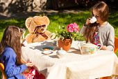 stock photo of little sister  - Two little sisters having english breakfast with teddy bear at yard - JPG