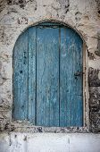 stock photo of dingy  - Old blue timber door in the scuffed wall rural scenery - JPG