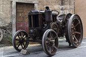 stock photo of tractor  - Old Italian tractor parked in the streets of the town - JPG