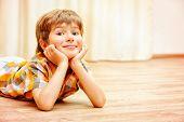 foto of linoleum  - Happy smiling boy lying on a floor at home - JPG
