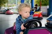 pic of carnival ride  - a little boy driving a bumper car at the carnival - JPG