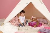 stock photo of teepee  - Toddler child kid engaged in pretend play with stuffed toys and teepee tent - JPG