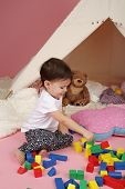foto of teepee tent  - Toddler child kid engaged in pretend play with building blocks toys and teepee tent - JPG