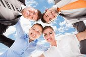 pic of huddle  - Directly below portrait of happy business people forming huddle against sky - JPG
