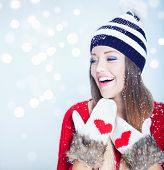 pic of beanie hat  - Beautiful happy young woman wearing winter hat and gloves covered with snow flakes - JPG
