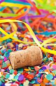 stock photo of champagne color  - Champagne cork and party streamers on colorful confetti - JPG