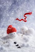 foto of snowmen  - Melting snowman with red knitted scarf blowing in the wind  - JPG