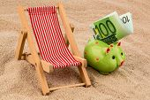 stock photo of currency  - beach chair with euro currency on the sandy beach - JPG