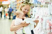 picture of apparel  - woman choosing children apparel with little baby child girl on hands in clothing shop supermarket - JPG
