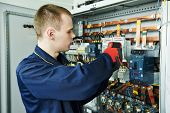 stock photo of boiler  - electrician inspector cheching power of fuseboard equipment in boiler room - JPG