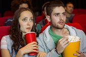 stock photo of cinema auditorium  - Young couple watching a film at the cinema - JPG