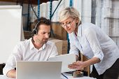 stock photo of warehouse  - Warehouse manager showing something to her colleague in a large warehouse - JPG