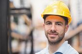 image of hard-on  - Close up portrait of worker wearing hard hat in the warehouse - JPG