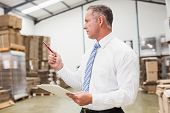 picture of warehouse  - Warehouse boss checking his inventory in a large warehouse - JPG