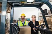 stock photo of forklift driver  - Warehouse manager smiling at camera with forklift driver in a large warehouse - JPG
