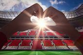 picture of love making  - Woman making heart shape with hands against football stadium full of england fans - JPG
