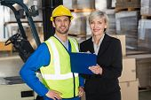 stock photo of forklift driver  - Forklift driver and his manager smiling at camera in a large warehouse - JPG