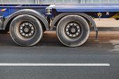 stock photo of fragmentation  - Fragment of truck wheels on dark asphalt road - JPG