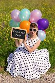 image of pinup girl  - Pinup Girl with balloons in the nature holding a slate with text Rock  - JPG